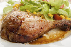 Roast chicken leg with salad. Close-up of a roast chicken leg with mixed salad and sauce in a dish stock photography