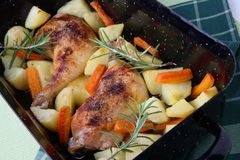 Roast chicken legs with potatoes and vegetable Stock Image