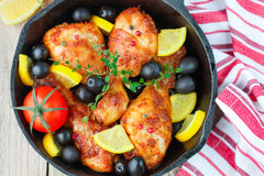 Roast chicken with lemon, olives, tomatoes and thyme. Dinner Royalty Free Stock Photos