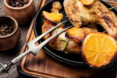 Roast chicken with orange. Baked chicken drumsticks with orange sauce in skillet royalty free stock photography