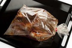 Roast chicken into a oven bag. On a baking tray royalty free stock images