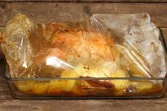 Roast chicken into a oven bag Stock Photos