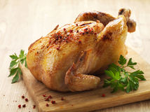 Roast chicken. And parsley on wooden cutting board royalty free stock photography