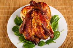Roast Chicken on Plate Garnished with Spinach Leaves Stock Photos