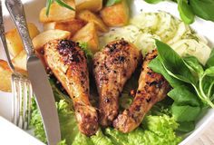Roast chicken with potatoes and cucumber Stock Photos