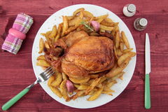 Roast chicken and potatoes on the rustic table Royalty Free Stock Images