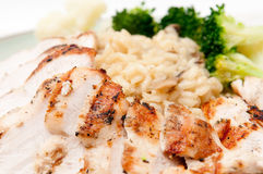 Roast chicken with risotto. Roasted chicken sliced and presented with mushroom risotto and broccoli and cauliflower. A heart healthy meal Royalty Free Stock Image