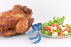 Roast Chicken and Salad. Roast chicken with a tape measure and salad on a white background royalty free stock photography