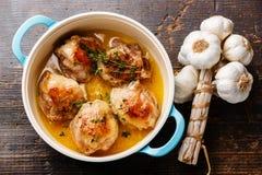 Roast chicken stew. In casserole and garlic on wooden background Stock Images