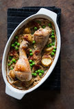 Roast chicken thigh. With peas, potatoes and bacon royalty free stock photo