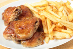 Roast chicken thighs and fries high angle Royalty Free Stock Image