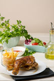 Roast chicken thighs and fries, and salad of lettuce and tomato Royalty Free Stock Photo