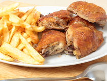 Roast chicken thighs and fries with spoon Royalty Free Stock Photo