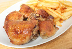Roast chicken thighs and fries with spoon Royalty Free Stock Image