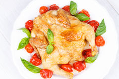 Roast chicken with tomatoes cherry, green basil and garlic. Stock Photo