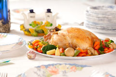 Roast Chicken and vegetables. A whole fully roasted chicken with vegetables on a white tablecloth Royalty Free Stock Images