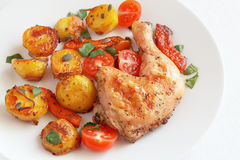 Roast of chicken and vegetables with fresh cherry tomatoes, cilantro, and pumpkin seeds Stock Image