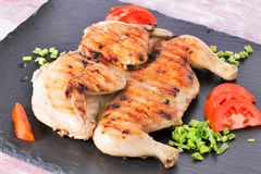 Roast chicken with vegetables. A chicken on a grill with segments of tomato and green onions, a toasted crisp crust. Close up, selective focus stock photography