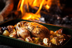 Roast chicken. A whole roast chicken in pan with potatoes and a fireplace in the background stock image