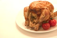 Roast Ckicken. Roast chicken on a plate with tomatoes Royalty Free Stock Images