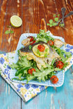 Roast Cod with lemon, garlic and vegetables Royalty Free Stock Images