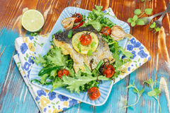 Roast Cod with lemon, garlic and vegetables Royalty Free Stock Photos