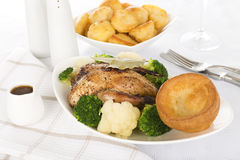 Roast Dinner. Roast partridge served with cauliflower, broccoli, roast potatoes and a jug of gravy. Traditional British Sunday and Christmas meal stock photography