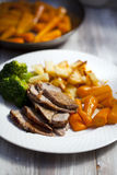 Roast dinner. Roast lamb with potatoes, carrots and broccoli stock photography