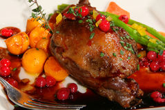 Roast duck. Confit leg of roast duck on a bed or red currents and roasted vegetables Royalty Free Stock Photography