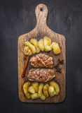 Roast duck breast with apples and cloves  cutting board on wooden rustic background top view close up Royalty Free Stock Images