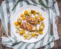 Roast duck breast with pear and peach on a white plate with knife fork striped napkin  wooden rustic background top view Royalty Free Stock Images