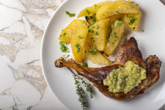 Roast duck with golden potatoes and garlic sauce with herbs on p Royalty Free Stock Photo