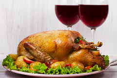 Roast duck with potato, apples, salad, thyme and rosemary. Two glasses of red wine Stock Image