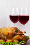 Roast duck with potato, apples, salad, thyme and rosemary. Two glasses of red wine Stock Photo