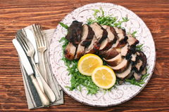 Roast fillet leg of lamb with greens and lemon Stock Photo