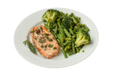 Roast fish with green vegetables on a white plate isolated Stock Photography