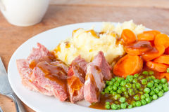 Roast Gammon Dinner. An overhead view of a roast gammon dinner on a white plate with a gravy boat in the background Stock Photo