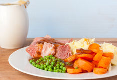 Roast Gammon Dinner. A roast gammon dinner on a white plate with a gravy boat in the background Royalty Free Stock Photography