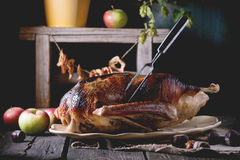 Roast goose with apples. Roast stuffed goose with meat fork in on ceramic plate with ripe apples over wooden kitchen table. Dark rustic style Stock Photo