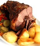 Roast lamb. Roast herb-coated lamb  with roasted potatoes and stir-fried vegetables Royalty Free Stock Image