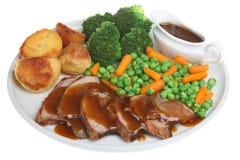 Roast Lamb Dinner. Traditional Sunday roast lamb dinner with individual gravy boat Stock Photo