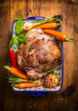 Roast lamb leg with vegetables and fresh herbs in blue casserole bowl on rustic wooden background Royalty Free Stock Photography