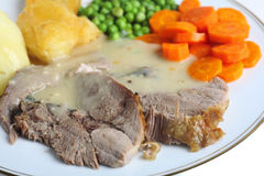 Roast lamb meal. A meal of roast lamb with roasted potatoes, boiled peas and boiled sliced carrots royalty free stock images