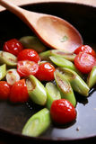 Roast leek and tomatoes. In frying pan Royalty Free Stock Photo