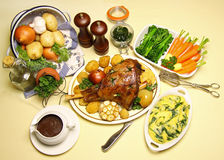 Roast Leg Of Lamb. Roasted leg of lamb with vegetables, mint jelly, gravy and spinach polenta stock photos
