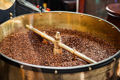 Roast machine. The freshly roasted coffee beans from a coffee roaster being poured into the cooling cylinder. The freshly roasted coffee beans from a coffee stock image