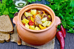 Roast meat and potatoes in clay pot on dark board Royalty Free Stock Photos