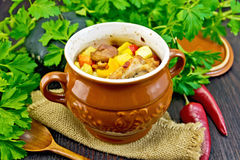 Roast meat and potatoes in pot on board Royalty Free Stock Images