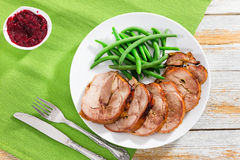 Roast meat roulade cut in slices with boiled green beans Stock Images