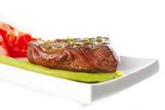 Roast meat served with tomato Royalty Free Stock Photo